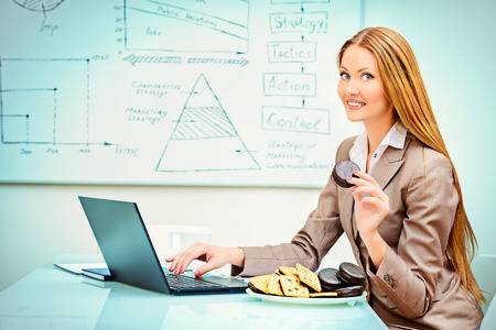 workplace wellness: Beautiful businesswoman working in the office with a laptopn and eating cookies.
