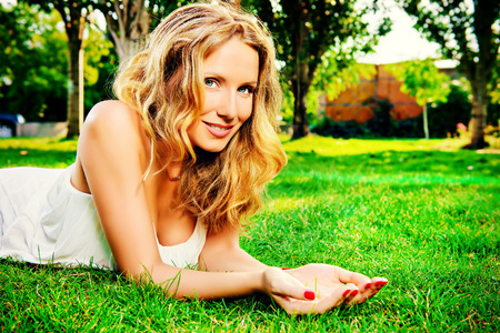 stress free: Close-up portrait of a beautiful smiling woman lying on a grass outdoor. She is absolutely happy. Stock Photo