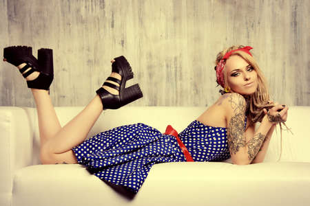 Pretty pin-up girl in old-fashioned polka-dot dress and modern hairstyle dreadlocks. Fashion shot. Mixture of styles. photo
