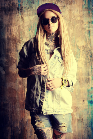 modern generation: Modern teenage girl with blonde dreadlocks over grunge background. Jeans style. Modern generation.