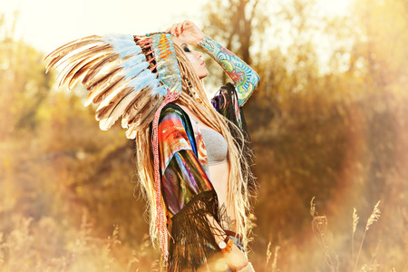 ceremonial make up: Close-up portrait of a beautiful girl wearing native american indian chief headdress. Western style. Jeans fashion.