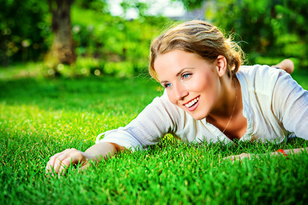 Close-up portrait of a beautiful smiling woman lying on a grass outdoor. She is absolutely happy. photo