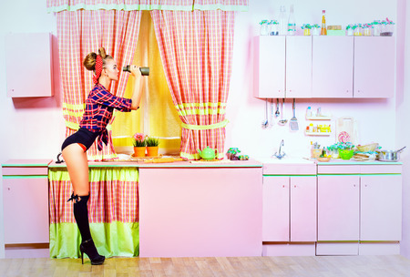 retro housewife: Lovely pin-up girl stands on a pink kitchen and through binoculars. Retro style. Fashion.