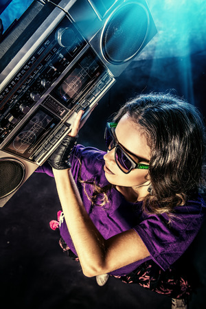 Portrait of a modern girl with tape recorder over grunge background. Street urban style. photo