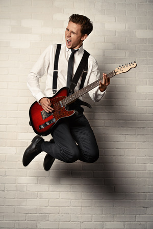 guitarists: Expressive young man playing rock-n-roll music on his electric guitar. Retro, vintage style.