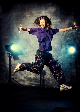 Beautiful hip-hop dancer jumping over grunge background. photo