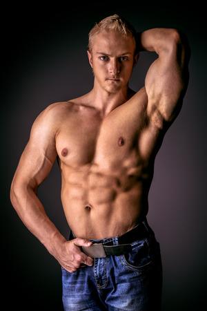 male torso: Muscular bodybuilder man posing over dark background. Mens beauty. Sports.