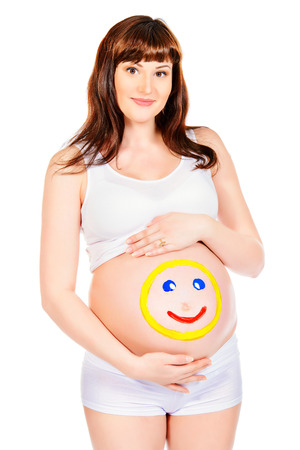 Smiling pregnant woman  with drawn funny face on her belly. Pregnancy. Healthcare. Studio shot. photo