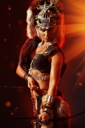 warrior woman: Beautiful bellicose Amazon with bow and arrows in battle. Ancient times. Stock Photo