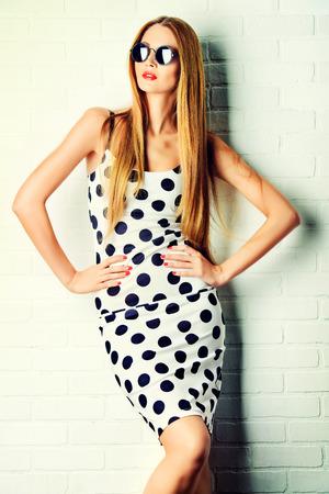 mujeres fashion: Señora de moda en lunares vestido posando cerca de la pared de ladrillo blanco. Belleza, concepto de moda. Óptica.