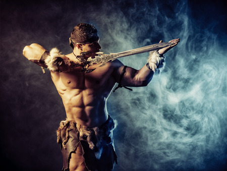 historical battle: Portrait of a handsome muscular ancient warrior with a sword.