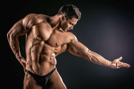 muscle: Culturista musculoso guapo posando sobre fondo negro.
