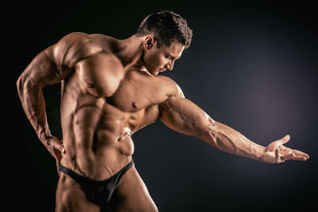 arm muscles: Handsome muscular bodybuilder posing over black background.