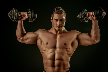 heavy lifting: Portrait of a handsome muscular bodybuilder posing with dumbbells over black background.