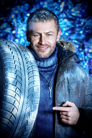 Handsome brutal man dressed in winter clothes covered with frost standing with car tire. photo