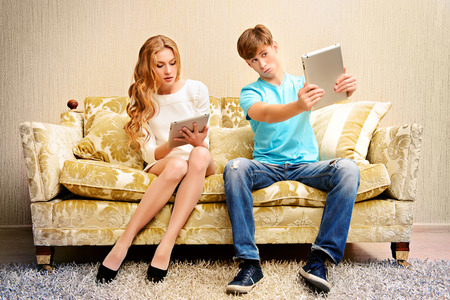 Young woman and a man sitting on a sofa and each of them looks at his own digital tablet. photo