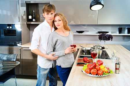 family kitchen: Happy young couple in love cooking a dinner on a kitchen and drink red wine.