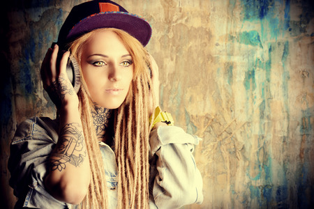 personas escuchando: Adolescente de moda con rastas rubias escuchando m�sica en los auriculares. Foto de archivo
