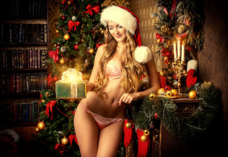 Red panties: Attractive girl in sexual lingerie gives a gift for Christmas. Christmas decoration. Stock Photo