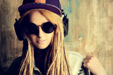 modern generation: Adolescente de moda con rastas rubias escuchando m�sica en los auriculares. Estilo Jeans. Generaci�n moderna.
