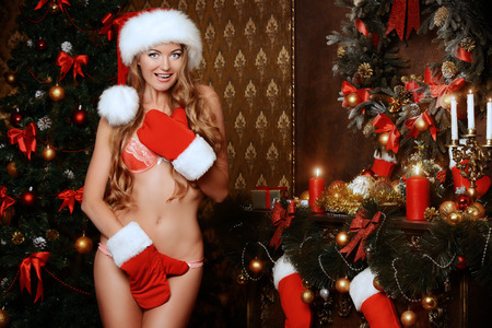 nude babe: Attractive Christmas girl in a sexual lingerie covers herself with mittens and smiles.