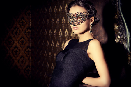 black dress: Beautiful mysterious stranger girl in venetian mask. Carnival, masquerade. Jewellery, gems. Stock Photo