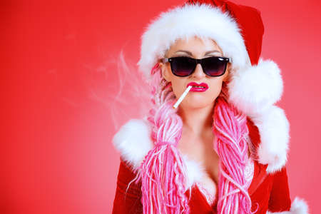 santa girl: Smoking girl in Santa Claus costume posing over red background. Christmas.