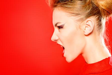 mujer enojada: Moda foto de un modelo de mujer impresionante en vestido rojo posando en el estudio sobre fondo rojo Foto de archivo