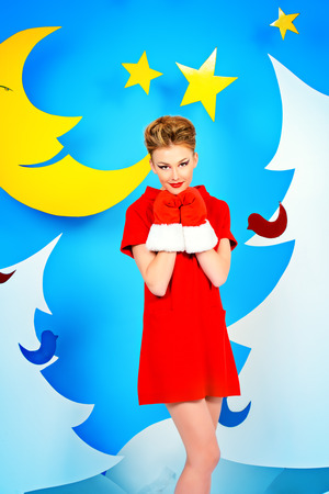 woman red dress: Attractive young woman in festive red dress posing in Christmas decorations