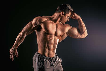 muscle building: Handsome muscular bodybuilder posing over black background.