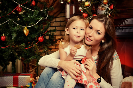 miracle tree: Mother and daughter on the background of the Christmas tree Stock Photo