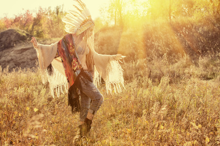 western clothing: Beautiful girl in style of the American Indians dancing in the rays of the autumn sun. Western style. Jeans fashion.