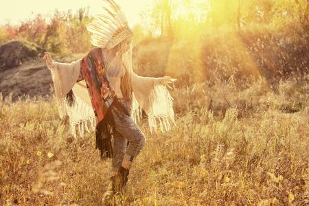 gente bailando: Muchacha hermosa en estilo de los indios americanos bailando en los rayos del sol de otoño. Estilo occidental. Jeans de moda. Foto de archivo