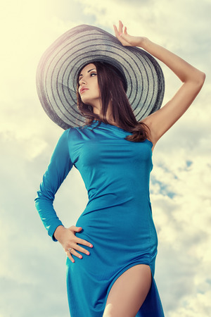 Portrait of a charming lady in beautiful elegant dress and hat against the sky. photo