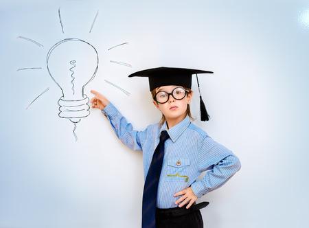 ni�os inteligentes: Muchacho elegante destaca por la pizarra en un aula que expresa la nueva idea. Concepto educativo. Copiar el espacio.