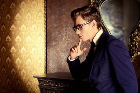 respectable: Handsome respectable man in elegant suit stands in a room with classic vintage style. Business. Fashion.