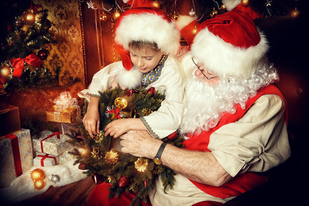 Santa Claus in his everyday clothes in Christmas home décor. Happy little boy helps Santa Claus get ready for Christmas. photo