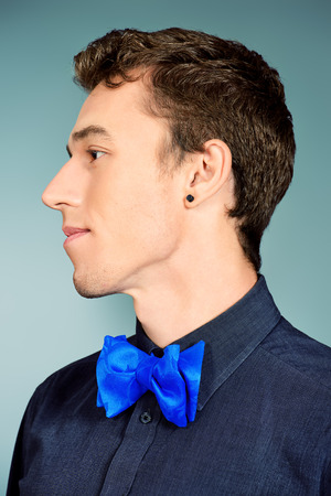 imposing: Close-up portrait of an imposing young man in formal shirt and bow-tie. Mens beauty, fashion.