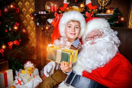 Happy little boy sitting on the lap of Santa Claus and rejoice a gift. Christmas decoration. photo