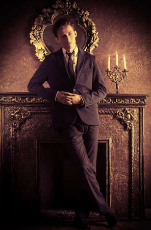 respectable: Young handsome man in elegant suit stands by the fireplace in a room with classic vintage style. Fashion. Stock Photo