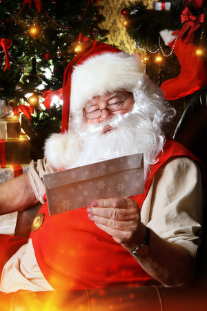 Santa Claus reading letters from children. He is at home, decorated for Christmas. Santas mail. photo