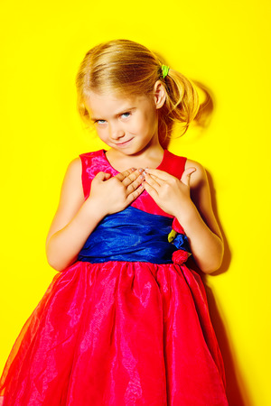 Pretty little girl posing in bright pink dress over yellow background. Fashion shot. Childhood. photo