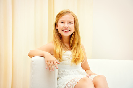 homey: Teen girl sitting on a couch at home and smiling at camera.