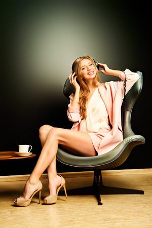 sexy headphones: Beautiful smiling girl enjoying listening to music in headphones. Interior, furniture. Leisure. Stock Photo