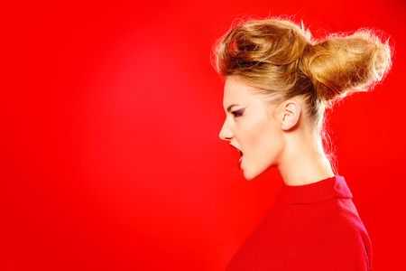 Fashion shot of a stunning female model in red dress posing at studio over red background. Beauty, fashion. photo
