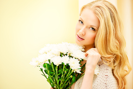 Pretty young woman sitting on a sofa at home, holding white flowers and smiling. Interior. photo