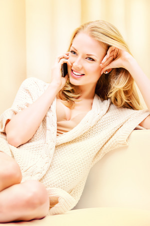 Beautiful young woman talking on the phone and smiles. She is at home. photo