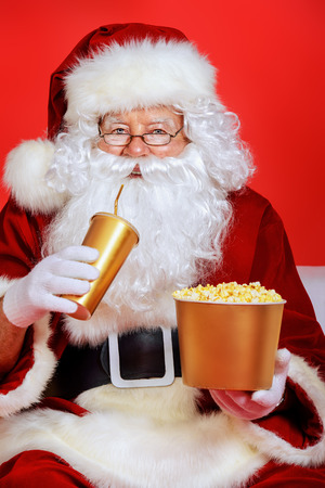drinking soda: Close-up portrait of Santa Claus eating popcorn and drinking soda. Christmas. Red background.