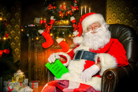 Santa Claus brought gifts for Christmas and having a rest by the fireplace. Home decoration. photo
