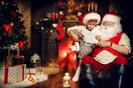home decorated: Little boy and Santa Claus reading letters from children. They are at home, decorated for Christmas. Santas mail.